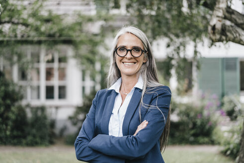 Portrait of smiling businesswoman  wearing spectacles standing in the garden - KNSF000362