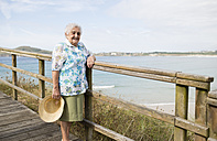 Happy senior woman standing on boardwalk - RAEF001420