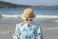 Back view of senior woman wearing straw hat on the beach looking at distance - RAEF001429