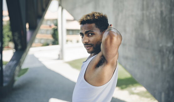 Portrait of young man doing stretching exercises - DAPF000288