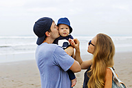 Indonesia, Bali, Happy parents with baby at the beach - KNTF000463