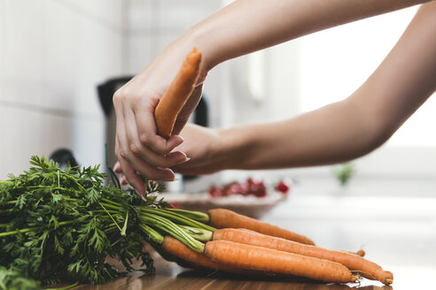 Woman removing leaves from bunch of carrots - MIDF000783