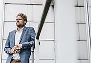 Businessman leaning on railing - KNSF000375