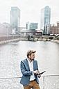 Businessman standing on bridge using tablet - KNSF000381