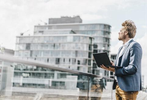 Businessman standing on bridge using laptop - KNSF000387
