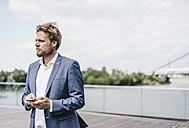 Businessman standing on bridge holding cell phone - KNSF000405