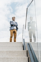 Businessman standing atop of stairs - KNSF000423