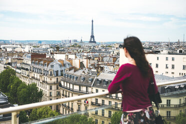 France, Paris, woman enjoying the view of Paris with the Eiffel Tower in the background - GEMF000970