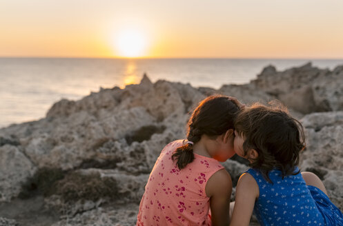 Back view of two little sisters sitting at rocky coast by sunset - MGOF002250