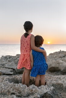 Back view of two little sisters standing side by side at rocky coast watching sunset - MGOF002253
