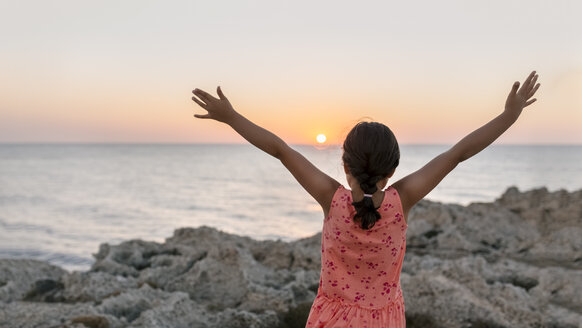 Back view of little girl with raised arms at rocky coast by sunset - MGOF002256