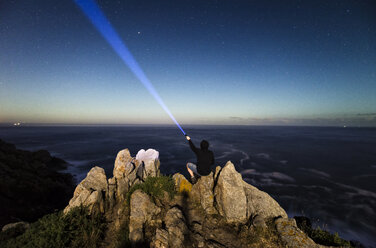 Man sitting on rocks in the coast and lighting up the sky with a flashlight - RAEF001437