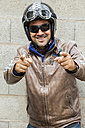 Smiling biker wearing sunglasses and helmet pointing on viewer - JUNF000584