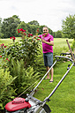 Smiling man caring for his roses in the garden - JUNF000587