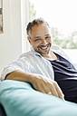 Portrait of smiling man sitting on the couch at home - JUNF000596