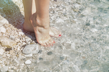 Feet of young woman at water'se dge - JUNF000608