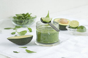 Glass of spinach avocado lime smoothie and ingredients - ASF005982