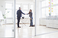Businessman and woman shaking hands in bright office - RBF004988