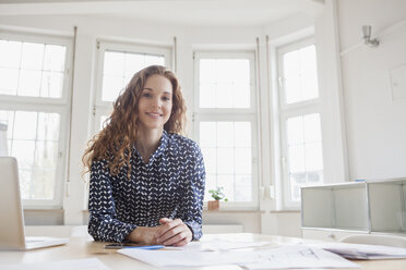 Portrait of smiling woman at desk in office - RBF005003