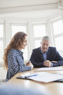 Businessman and woman at desk discussing plans - RBF005009
