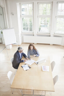 Businessman and woman in boardroom - RBF005012