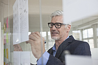 Businessman in office writing on paper at glass pane - RBF005036
