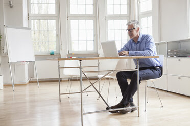 Mature businessman using laptop in bright office - RBF005045