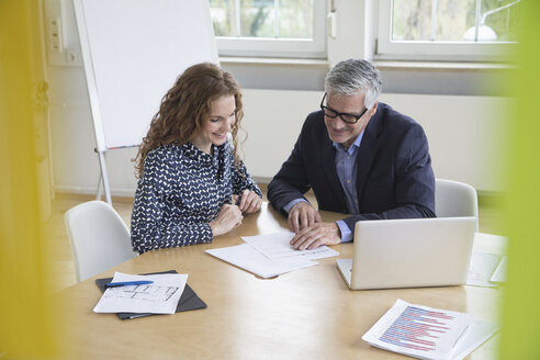 Businessman and woman sitting at boardroom table looking at documents - RBF005063