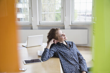 Smiling woman in office leaning on table - RBF005069
