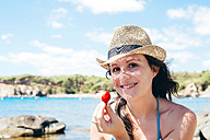 Portrait of smiling woman wearing straw hat on the beach holding strawberry - GEMF000979