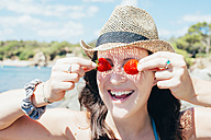 Portrait of smiling woman wearing straw hat on the beach covering her eyes with strawberries - GEMF000982