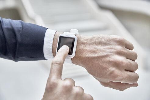 Businessman touching smartwatch - FMKF002886