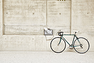 Bicycle at concrete wall and bag in ledge - FMKF002889