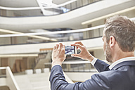 Businessman taking cell phone picture in modern office building - FMKF002901