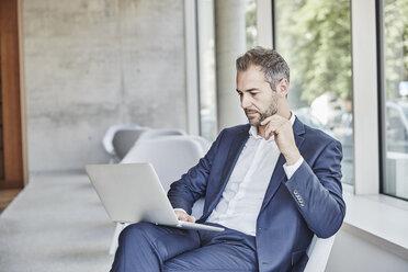 Businesssman sitting using laptop - FMKF002928