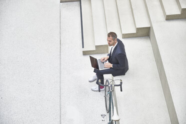 Businesssman on stairs using laptop next to bicycle - FMKF002931