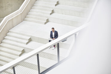 Businesssman sitting on stairs using laptop - FMKF002940