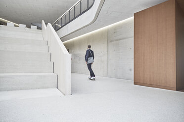 Businesssman riding skateboard along concrete wall in office building - FMKF002946