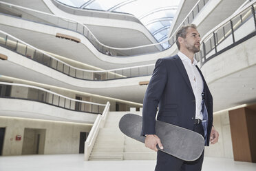 Businesssman standing with skateboard in office building - FMKF002949