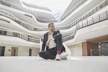 Smiling businessman sitting on the floor in office building - FMKF002952
