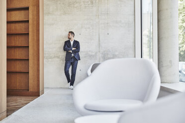 Businesssman leaning against concrete wall - FMKF002955