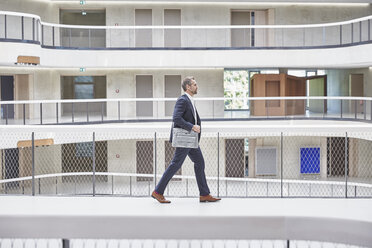 Businesssman walking with bag in modern office building - FMKF002961