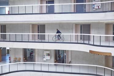 Businesssman riding bicycle in modern office building - FMKF002964