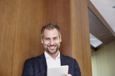 Portrait of smiling businessman holding tablet - FMKF002967