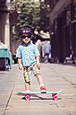 Portrait of little boy with skateboard wearing oversized sunglasses and basecap - XCF000096