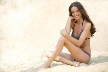 Young woman sitting on sand, bikini - MAEF011940