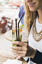 Woman holding glass of Mojito - JUNF000612
