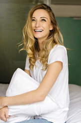 Laughing blond woman sitting on bed holding cushion - JUNF000615