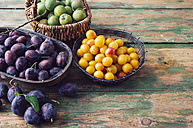 Baskets of plums, mirabelles and greengages on wood - PPXF000025