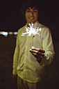 Man holding sparkler on the beach at night - DAPF000296